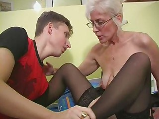 Mature with Silver Hair Glasses and Stockings Wakes the Lad