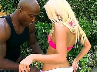 Blond hottie Jessie Volt kneels and deep blows this dark men huge cock